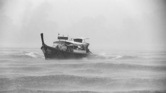 boat floating in stormy ocean
