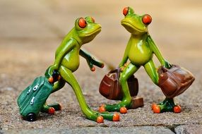 figures of frogs with suitcases