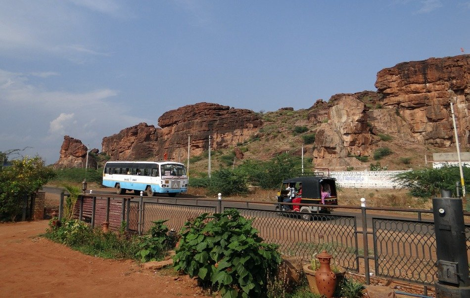 transport on road at red sand stone rocks, india, badami