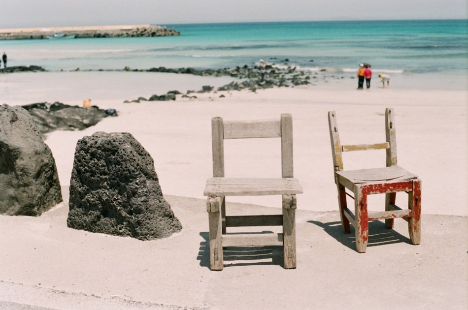wooden chairs on the beach of jeju island
