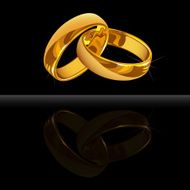 Gold wedding rings on black background with reflection