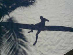shadow in the sand in the form of a man on a tree trunk