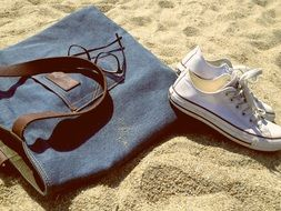 bag and sports shoes on the beach