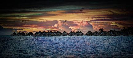 bora sunset over water bungalows in ocean