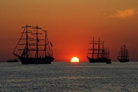 big sailing ships at sunset sea
