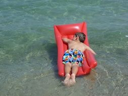 child on an inflatable mattress on the beach