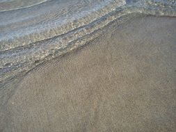clear waves splashing on grey sand beach
