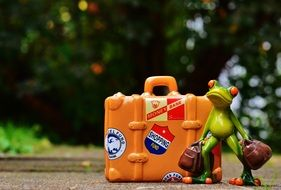 Toy frog with big suitcase