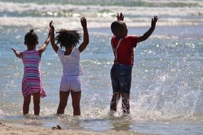 African children are splashing in the water on the ocean