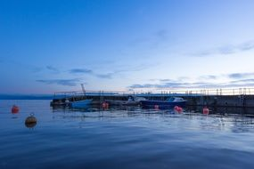 blue hour, boats and buoys at pier on calm water