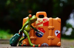 Toy frog with a suitcase on holiday