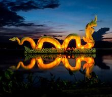 illuminated dragon figure on the lake at dusk