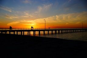 people on jetty pier sunset panorama