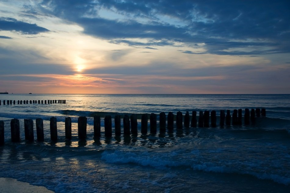 sunset over the baltic sea with breakwaters