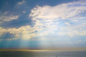 sun rays bursting through clouds above sea at morning
