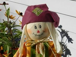 cute scarecrow on flower bed at autumn
