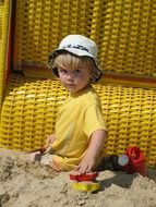 child plays with toys in the sand
