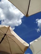 beach parasols at blue sky, bottom view
