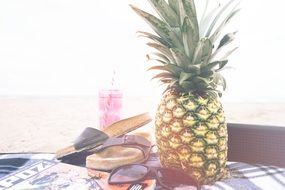 pineapple, beach slippers and sunglasses