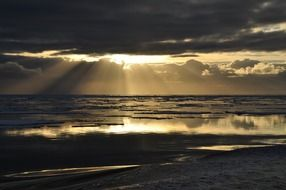 sunbeams through dark clouds in sunset seascape