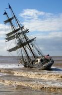 leaning sailing ship on stormy sea at coast