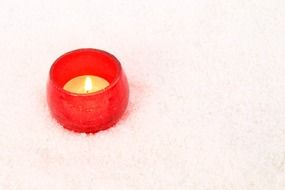 burning candle in red pot closeup