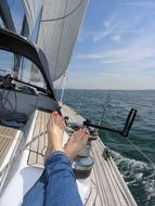 female legs on a sailing boat in the sea