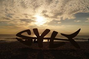 sylt, fish form modern art object silhouette on sunset beach, germany