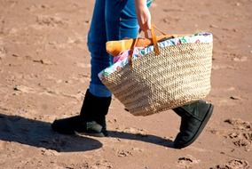 man with a woven bag goes in the sand