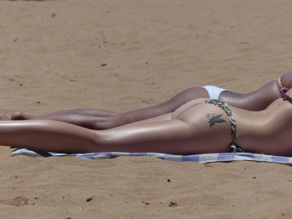 girl with a tattoo sunbathes on the beach