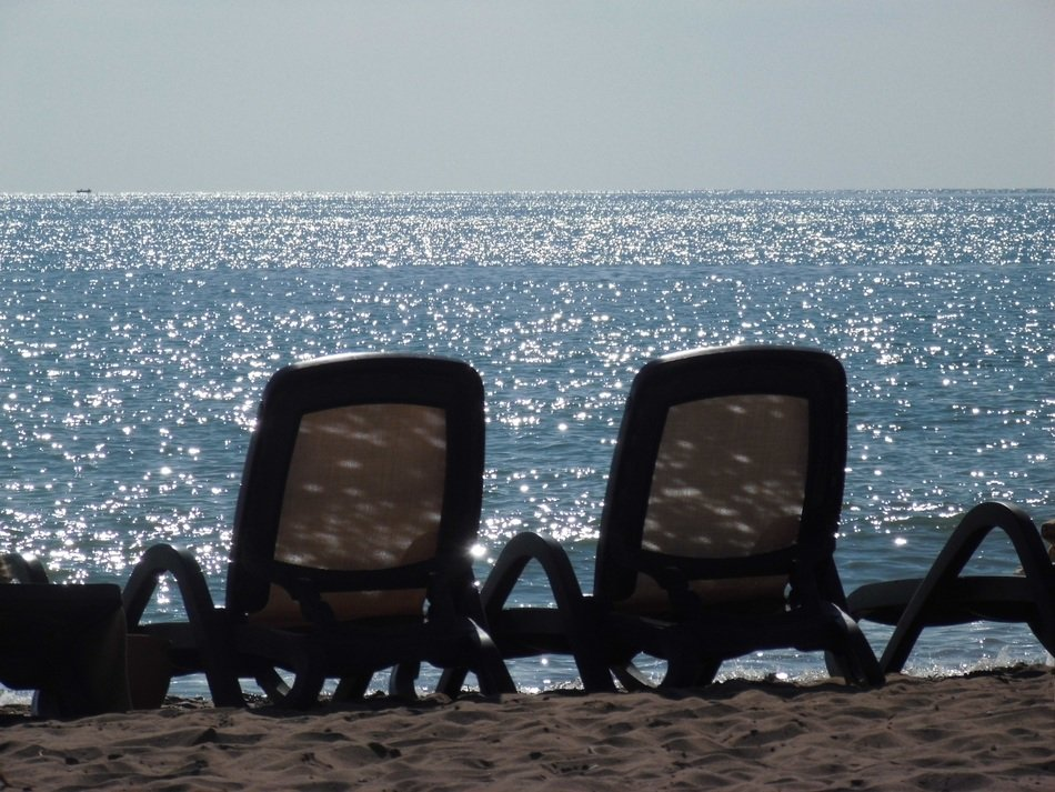 deck chairs on a sand beach on a sunny day