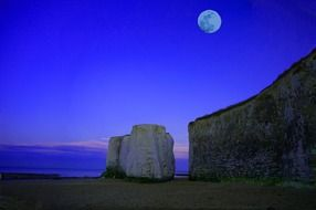 full moon above sea and chalk cliffs on beach, scenic night landscape