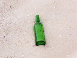 empty green bottle on sandy beach