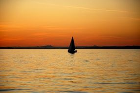 Lonely sailboat on the lake at sunset