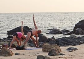 man and woman practicing yoga on beach at sea