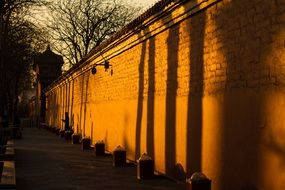 sunset light and shadow on aged stone wall, china, beijing