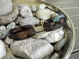 sunglasses lie on the stones