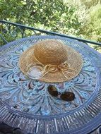 sun hat and glasses on vintage round table outdoor