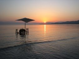 table and chairs beneath parasol in water at sunrise, greece, corfu, roda