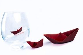Red paper boats with one boat inside the vase with water