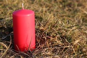 red candle on the grass