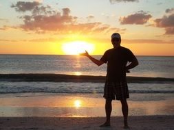 man holding the sun on the beach