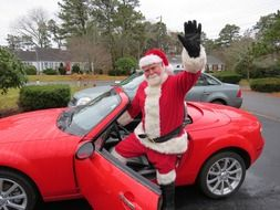 Santa Claus sits in a sports red car