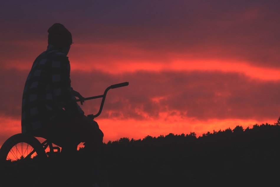 dark male silhouette on bicycle at red sunset sky