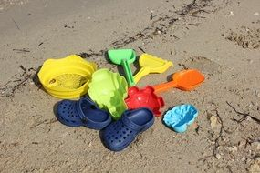 colorful beach toys and blue sandals on sand