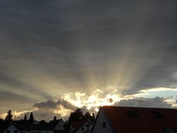 sunset rays under dark clouds