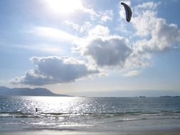 kitesurfing against the backdrop of the bright sun behind the clouds