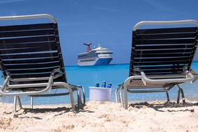 the Carnival Triumph cruise ship on sea in front of two chairs on beach, Bahamas, half moon cay
