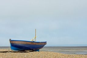 blue wooden fishing boat on the shore