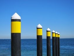 ocean yellow posts near water